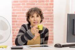 Mujer de mediana edad encantadora que bebe un café Imagen de archivo