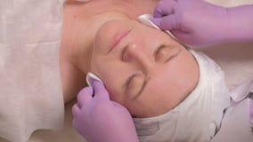Mujer de mediana edad europea en un procedimiento cosmético Un cosmetologist profesional en guantes de la lila limpia la piel de  metrajes