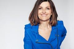 Mujer de mediana edad feliz en chaqueta azul. Fotos de archivo libres de regalías