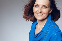 Mujer de mediana edad feliz en chaqueta azul. Fotografía de archivo