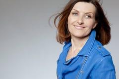 Mujer de mediana edad feliz en chaqueta azul. Imágenes de archivo libres de regalías