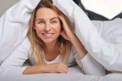 Mujer de mediana edad hermosa debajo de las hojas blancas Fotos de archivo libres de regalías