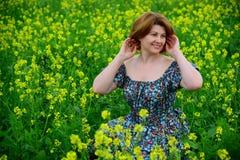 Mujer de mediana edad hermosa que se sienta en prado floreciente Imagenes de archivo