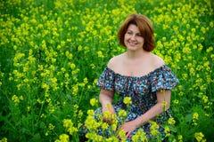 Mujer de mediana edad hermosa que se sienta en prado floreciente Foto de archivo