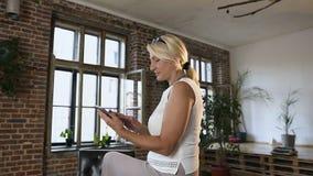 Mujer de mediana edad hermosa que usa la tableta mientras que se sienta en la tabla en la oficina Mujer rubia que enrolla las pág metrajes