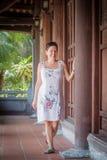 Mujer de mediana edad morena que camina abajo del pasillo con las columnas de madera Fotografía de archivo
