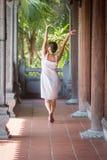 Mujer de mediana edad morena que camina abajo del pasillo con las columnas de madera Imagen de archivo