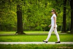 Mujer de mediana edad que camina en parque de la ciudad Imagenes de archivo