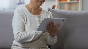 Mujer de mediana edad que charla en red social en la tableta, conectando con la familia almacen de video