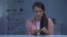Mujer de mediana edad que cuenta el dinero detrás de la ventana lluviosa, inseguridad social, pobreza metrajes