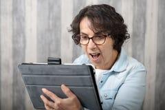 Mujer de mediana edad que hace una llamada distante en Internet imagen de archivo
