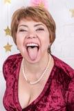 Mujer de mediana edad que muestra la lengua Fotos de archivo