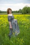 Mujer de mediana edad que se coloca en prado del verano Imagenes de archivo