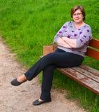 Mujer de mediana edad que se relaja en un banco de parque Imagen de archivo libre de regalías