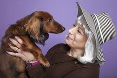 Mujer de mediana edad que sostiene un perro Fotografía de archivo libre de regalías