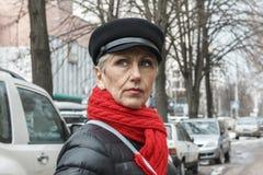 Mujer de mediana edad seria con las arrugas en la bufanda de la cara y del rojo C fotografía de archivo libre de regalías