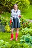 Mujer de mediana edad sonriente en botas de goma rojas que planta las flores Imagen de archivo