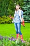 Mujer de mediana edad sonriente hermosa en un jardín de flores Foto de archivo