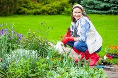 Mujer de mediana edad sonriente que trabaja en una cama de flor fotografía de archivo libre de regalías