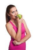 Mujer de mirada modelo que come una manzana Fotos de archivo