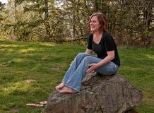 Mujer de mirada natural joven Laughin mientras que se sienta en la roca Barefo Imagen de archivo