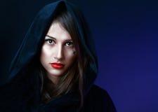 Mujer de Misteriouse en capo motor negro Imagenes de archivo