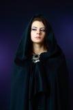 Mujer de Misteriouse en capo motor negro Imagen de archivo