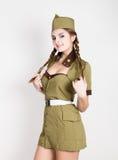 Mujer de moda atractiva en el uniforme militar y el forraje-casquillo, presentando fotografía de archivo
