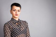 Mujer de moda con el pelo corto y vestida en una blusa para los lunares, colocándose en el fondo gris Fotos de archivo libres de regalías
