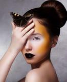 Mujer de moda con la mariposa. Brillantes creativos componen. Labios negros foto de archivo