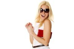 Mujer de moda con las gafas de sol que sostienen el bolso rojo Imagen de archivo