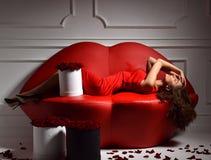 Mujer de moda de lujo hermosa que miente en el sofá rojo del sofá de los labios Foto de archivo libre de regalías