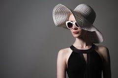 Mujer de moda hermosa joven con maquillaje de moda En cámara de mirada modelo, lentes elegantes que llevan, sombrero hembra Fotografía de archivo