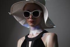 Mujer de moda hermosa joven con maquillaje de moda En cámara de mirada modelo, lentes elegantes que llevan, sombrero La moda feme Foto de archivo