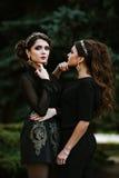 Mujer de moda hermosa joven dos en la ropa negra que presenta para el fotógrafo Vendas en la cabeza, en los oídos Fotos de archivo libres de regalías