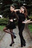 Mujer de moda hermosa joven dos en la ropa negra que presenta para el fotógrafo Vendas en la cabeza, en los oídos Foto de archivo libre de regalías