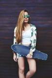 Mujer de moda joven en las gafas de sol que presentan con su longboard que disfruta de buen día en verano Imágenes de archivo libres de regalías