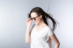 Mujer de moda joven en pelo de las gafas de sol en el viento Fotos de archivo