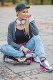 Mujer de moda linda que se relaja con su tablero del patín Fotos de archivo libres de regalías