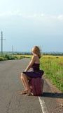 Mujer de moda que hace autostop en el borde de la carretera Imágenes de archivo libres de regalías