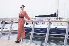 Mujer de moda que lleva el vestido rojo largo en las gafas de sol que toman un paseo cerca del mar, embarcadero con los yates Imagen de archivo libre de regalías