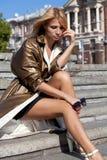 Mujer de moda que se sienta en las escaleras Imagen de archivo libre de regalías
