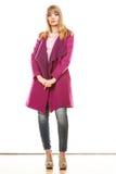 Mujer de moda rubia en capa viva del color Foto de archivo libre de regalías