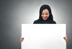 Mujer de negocios árabe que lleva a cabo a un tablero blanco aislado Imágenes de archivo libres de regalías