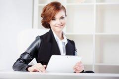 Mujer de negocios acertada con la tableta a disposición Imagenes de archivo