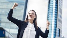 Mujer de negocios acertada con los brazos para arriba al aire libre Imágenes de archivo libres de regalías