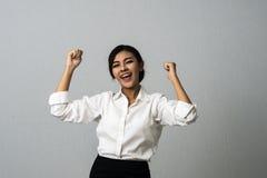 Mujer de negocios acertada con los brazos para arriba que celebra Imágenes de archivo libres de regalías