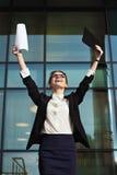 Mujer de negocios acertada con los brazos para arriba y los documentos Foto de archivo libre de regalías