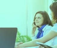 Mujer de negocios acertada con los colegas que hablan en el teléfono Fotografía de archivo libre de regalías