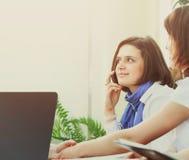 Mujer de negocios acertada con los colegas que hablan en el teléfono Imagen de archivo libre de regalías